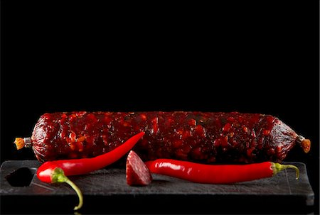 stick - Salami sausage and chili on old black plastic cutting board Stock Photo - Premium Royalty-Free, Code: 659-06903611
