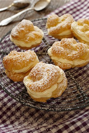 puff - Profiteroles dusted with icing sugar, on a cooling rack Stock Photo - Premium Royalty-Free, Code: 659-06903624