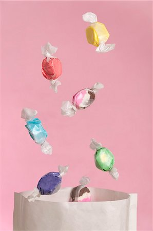 Sweets falling into a paper bag Stock Photo - Premium Royalty-Free, Code: 659-06903642
