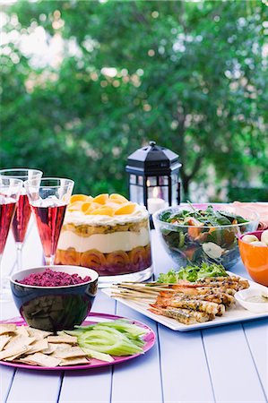 set - A table in the garden, laid with prawn skewers, beetroot dip, spinach salad and a trifle Stock Photo - Premium Royalty-Free, Code: 659-06903681