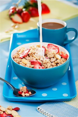 Milk being poured into a bowl of crunchy strawberry muesli Stock Photo - Premium Royalty-Free, Code: 659-07026971