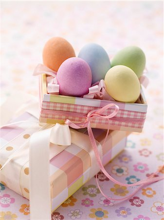An Easter parcel and brightly coloured eggs for Easter Stock Photo - Premium Royalty-Free, Code: 659-07027223