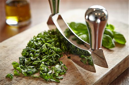 Basil being chopped with a curved chopping knife on a wooden board Stock Photo - Premium Royalty-Free, Code: 659-07027332