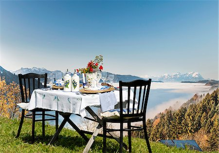 A table laid in the country house style, on an alpine meadow with a view over the Alps Stock Photo - Premium Royalty-Free, Code: 659-07027426