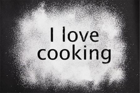 sugar - 'I love cooking' etched in icing sugar on a black background Stock Photo - Premium Royalty-Free, Code: 659-07027558