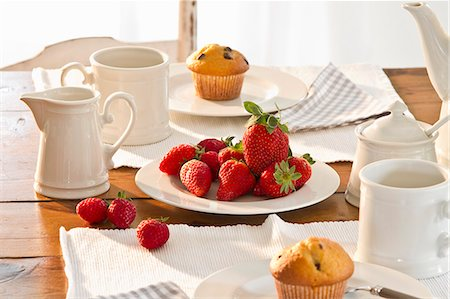 set - A table laid for coffee with muffins and fresh strawberries Stock Photo - Premium Royalty-Free, Code: 659-07027651