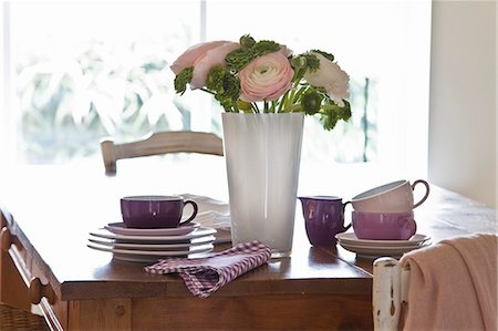 set - A wooden table with stacked crockery; in the centre is a decorative bunch of flowers including ranunculus Stock Photo - Premium Royalty-Free, Code: 659-07027669