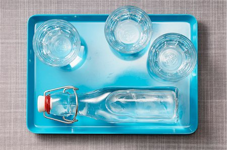 drinking water glass - Three glasses of water and a bottle of water on a blue tray Stock Photo - Premium Royalty-Free, Code: 659-07027937