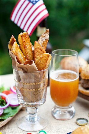 Potato wedges on a table outside, in the background buffalo burgers and a US flag Stock Photo - Premium Royalty-Free, Code: 659-07028365