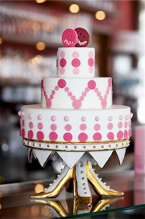 pink - An unconventional wedding cake decorated with pink buttons on a gilded cake stand Stock Photo - Premium Royalty-Free, Code: 659-07028420