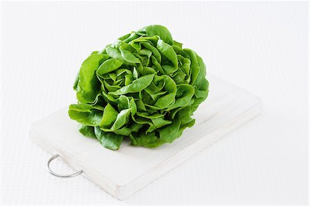 A lettuce on a chopping board against a white background Stock Photo - Premium Royalty-Free, Code: 659-07028592