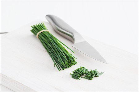 A bunch of chives and a knife on a chopping board Stock Photo - Premium Royalty-Free, Code: 659-07028593
