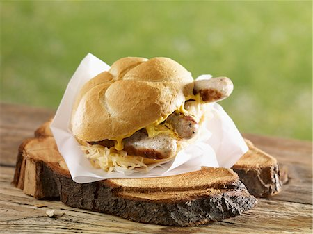 Bread roll filled with sauerkraut, grilled bratwurst and sausages Stock Photo - Premium Royalty-Free, Code: 659-07028749
