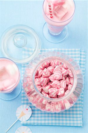 A jar of pink and white striped sweets, and a strawberry milkshake with marshmallows Stock Photo - Premium Royalty-Free, Code: 659-07028854