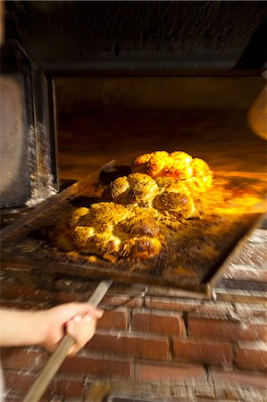 Freshly baked bread rolls on a baking tray in a wood-fired oven Stock Photo - Premium Royalty-Free, Code: 659-07068802