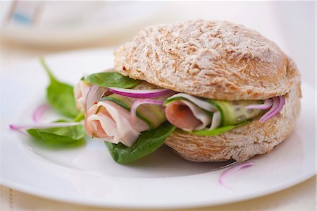 A sandwich filled with spinach, prosciutto, cucumber and onions Stock Photo - Premium Royalty-Free, Code: 659-07068844