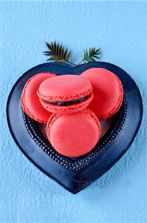 sweet - Raspberry macaroons with chocolate filling in a heart-shaped dish on a blue surface Stock Photo - Premium Royalty-Free, Code: 659-07068864