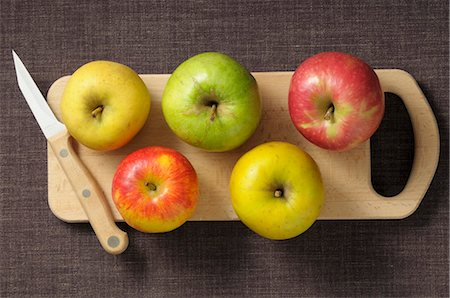 Assorted apples on a chopping board with a knife Stock Photo - Premium Royalty-Free, Code: 659-07068953