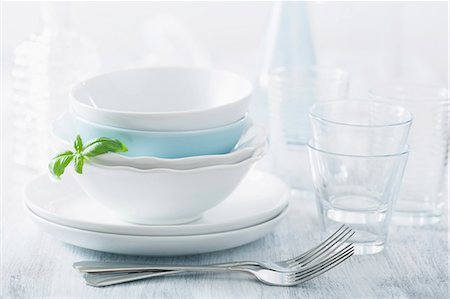 Stacked dinner bowls and plated, drinking glasses and forks Stock Photo - Premium Royalty-Free, Code: 659-07069253