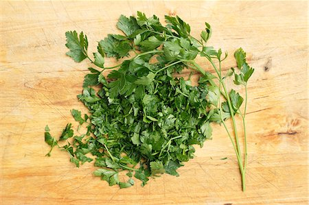 Fresh parsley, whole and chopped, on a wooden surface Stock Photo - Premium Royalty-Free, Code: 659-07069311