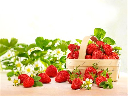 strawberries - Fresh strawberries with leaves, flowers and a woodchip basket Stock Photo - Premium Royalty-Free, Code: 659-07069356