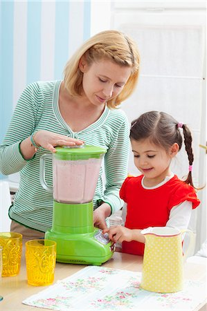A mother and daughter preparing a strawberry milkshake Stock Photo - Premium Royalty-Free, Code: 659-07069393