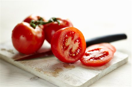 Sliced tomatoes and whole tomatoes on a board with a knife Stock Photo - Premium Royalty-Free, Code: 659-07069748