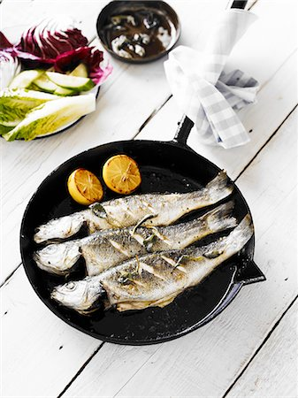 Three panfried whole bass, served in a cast-iron pan Stock Photo - Premium Royalty-Free, Code: 659-07597068