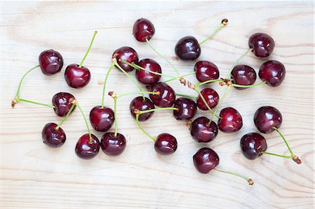 Cherries on a wooden surface Stock Photo - Premium Royalty-Free, Code: 659-07597087