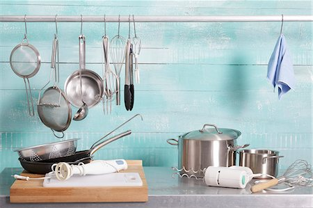 Assorted kitchen utensils on a stainless steel unit and hanging on a metal rod Stock Photo - Premium Royalty-Free, Code: 659-07597280