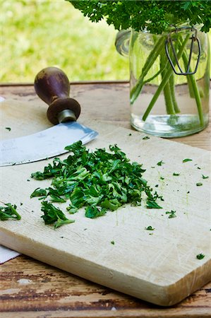 Chopped parsley with a mezzaluna on a wooden board Stock Photo - Premium Royalty-Free, Code: 659-07597312