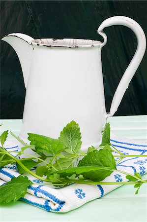 A still life featuring an enamel jug, lemon balm and an embroidered cloth Stock Photo - Premium Royalty-Free, Code: 659-07597499