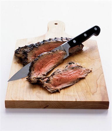 Sliced roast beef on a chopping board Stock Photo - Premium Royalty-Free, Code: 659-07597878