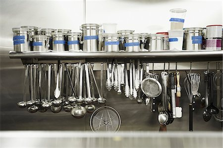 Professional Kitchen; Hanging Tools and Canisters of Seasonings Stock Photo - Premium Royalty-Free, Code: 659-07597959