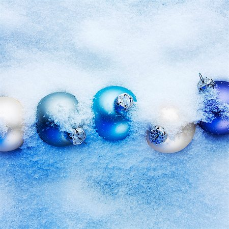 Blue and apricot-coloured Christmas baubles hidden in the snow Stock Photo - Premium Royalty-Free, Code: 659-07598318