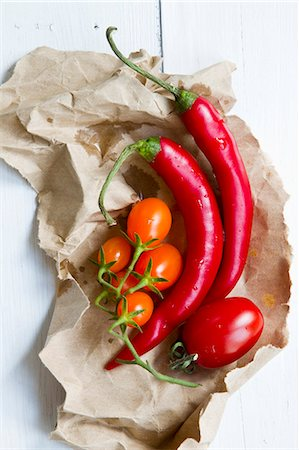 Whole chillies and tomatoes on paper Stock Photo - Premium Royalty-Free, Code: 659-07598332