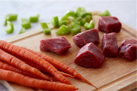 Chunks of Raw Beef, Raw Carrots and Chopped Celery on a Wooden Cutting Board Stock Photo - Premium Royalty-Free, Code: 659-07598521