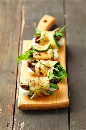 Grilled rolled slices of courgette filled with rocket, feta and sundried tomatoes Stock Photo - Premium Royalty-Free, Code: 659-07609816