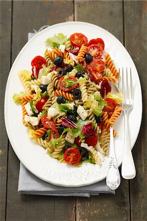 salad - Pasta salad with olives, cherry tomatoes, iceberg lettuce and mozzarella Stock Photo - Premium Royalty-Free, Code: 659-07609836