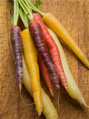 Multi-colored carrots in white, yellow, orange and red on a worn cutting board Stock Photo - Premium Royalty-Free, Code: 659-07610010