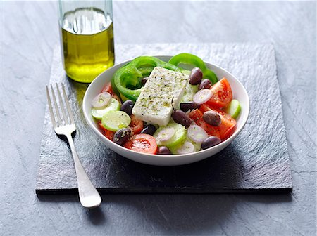 slate - A Greek salad next to a bottle of olive oil Stock Photo - Premium Royalty-Free, Code: 659-07610096