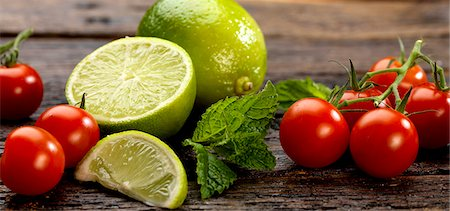 fresh - Cherry tomatoes, mint and limes on a wooden surface Stock Photo - Premium Royalty-Free, Code: 659-07610247