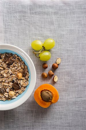 A bowl of muesli next to grapes, nuts and an apricot Stock Photo - Premium Royalty-Free, Code: 659-07610362