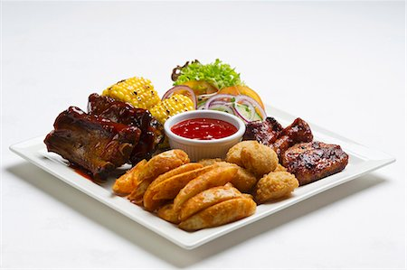 rib - Spare ribs and chicken wings with potato wedges, corn on the cob and ketchup Stock Photo - Premium Royalty-Free, Code: 659-07610407
