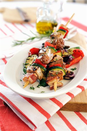 Barbecued kebabs with sausage, bacon and pancetta on grilled vegetables Stock Photo - Premium Royalty-Free, Code: 659-07738894