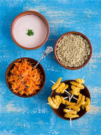 Chicken tandoori skewers with quinoa, carrot salad and raita in small bowls Stock Photo - Premium Royalty-Free, Code: 659-07739009