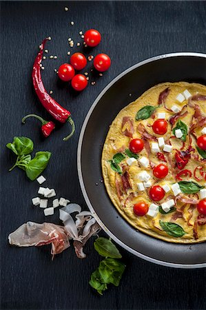 A breakfast omelette with tomatoes, feta cheese, ham and basil Stock Photo - Premium Royalty-Free, Code: 659-07739312