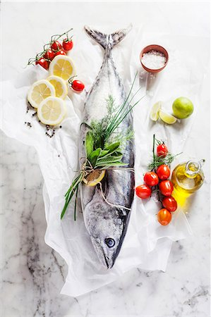 season - A whole tuna fish, cherry tomatoes, a bunch of herbs, lemons, olive oil and salt Stock Photo - Premium Royalty-Free, Code: 659-07739685