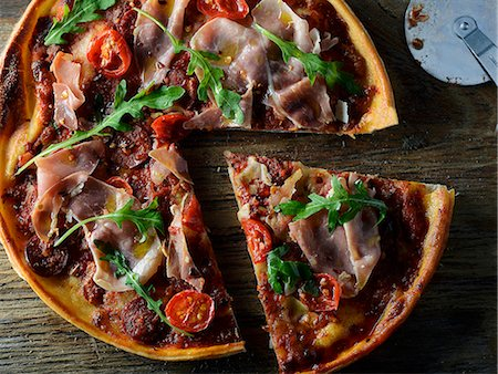 Pizza with Proscuitto, tomato and rocket, sliced Stock Photo - Premium Royalty-Free, Code: 659-07958371