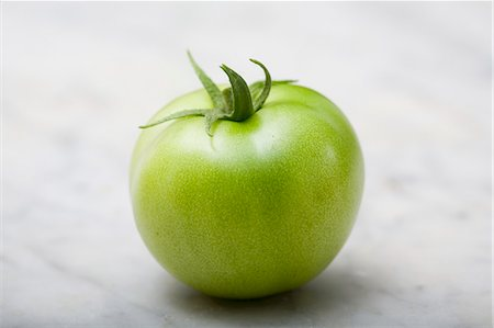 A green tomato on a marble platter Stock Photo - Premium Royalty-Free, Code: 659-07958893
